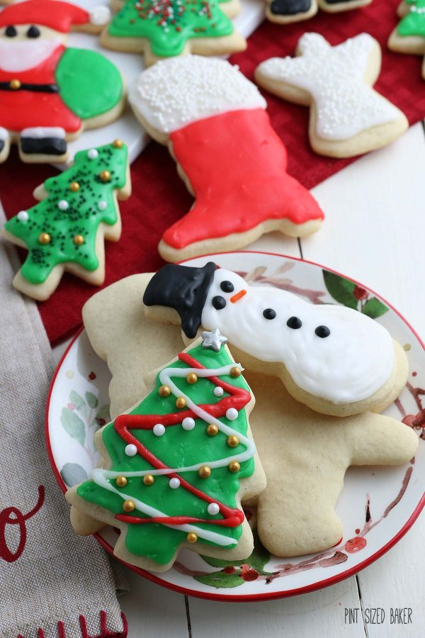 A close up image of a snowman and Christmas tree cut-out cookie decorated and ready to eat.