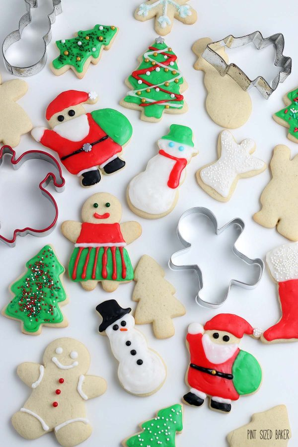 A Top down flat lay photo of cookie cutters, decorated cut-out cookies and undecorated holiday cookies.