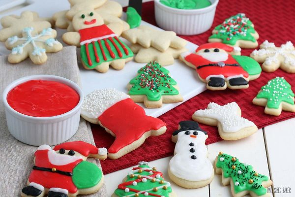 A Horizontal image of the Cut-Out Holiday Sugar Cookies on a red placemat.