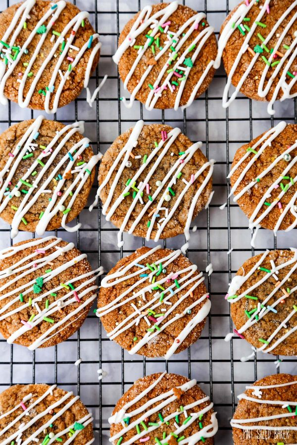 An overhead image of the crinkled, soft molasses cookies with icing drizzled over with a smattering of colored sprinkles.