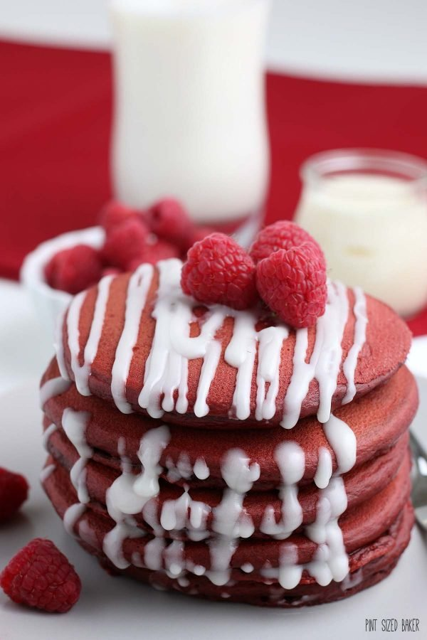 A close up image of the stack of red griddle cakes with the white cream cheese drizzle and fresh raspberries on top.