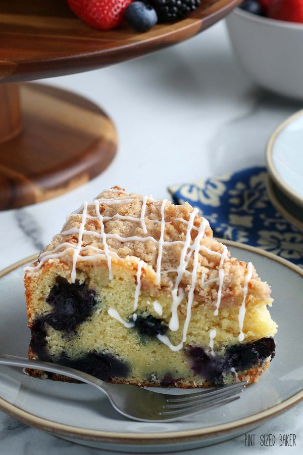 A close up image of the cake showing off the blueberries inside and the crumble and drizzle on top.