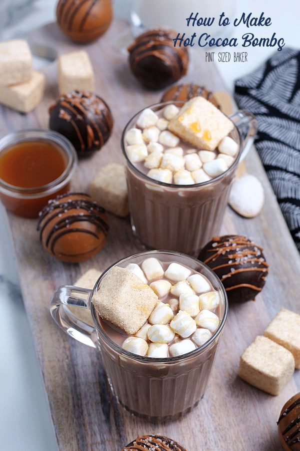 Image of hot  chocolate mugs with marshmallows on top and extra hot cocoa bombs, marshmallows and caramel sauce arounf them.