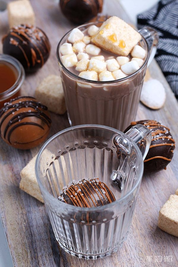 Image of a hot cocoa bomb inside a glass mug before hot milk is poured over top.