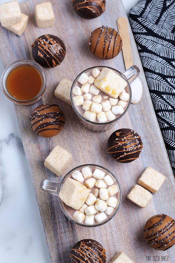 Lots of hot chocolate bombs on a wooden tray. Some bombs are dark brown from the chocolate wafers, others are light brown from the caramel wafers.