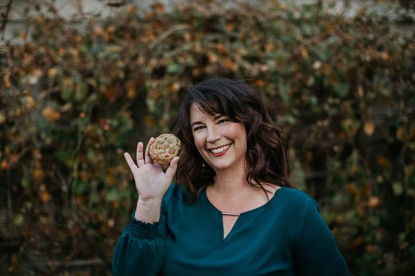 A photo of Karyn, the blogger behind Pint Sized Baker, holding a cookie.