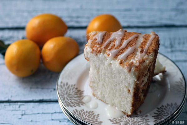 A slice of the angle food cake with a simple sugar glaze drizzled over.
