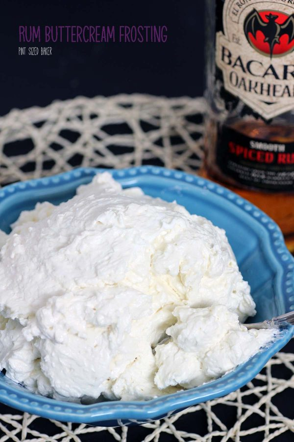 Lead in image of the Rum Buttercream in a blue bowl with the bottle of spiced rum in the background.