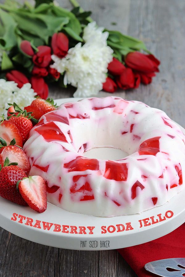 Lean in image of the red and white jello ring on a white serving dish with fresh cut strawberries and fresh flowers in the background.