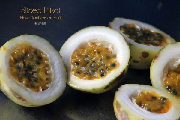 Sliced passion fruit showing off the edible fruit and seeds inside.