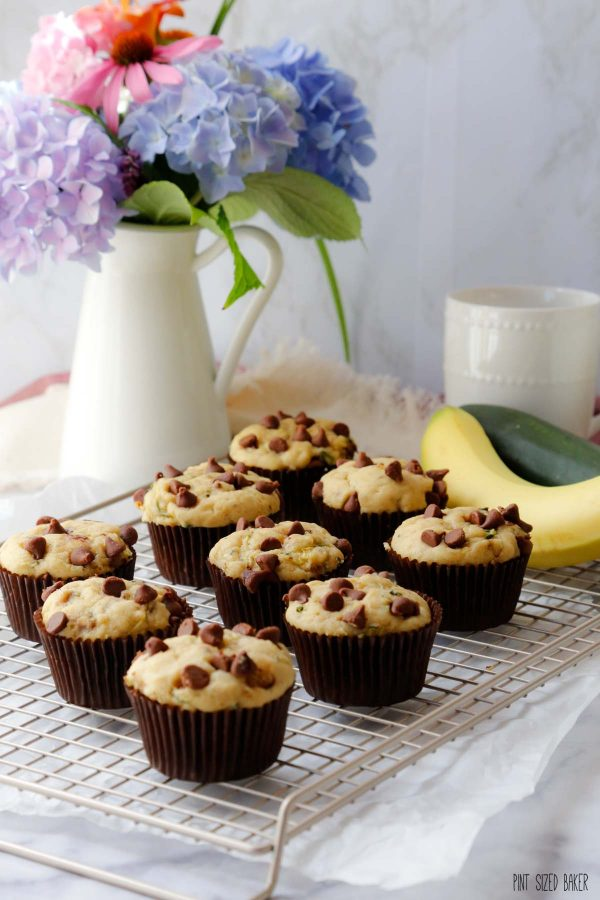 9 muffins on a cooling rack with a flower arrangement in the background.