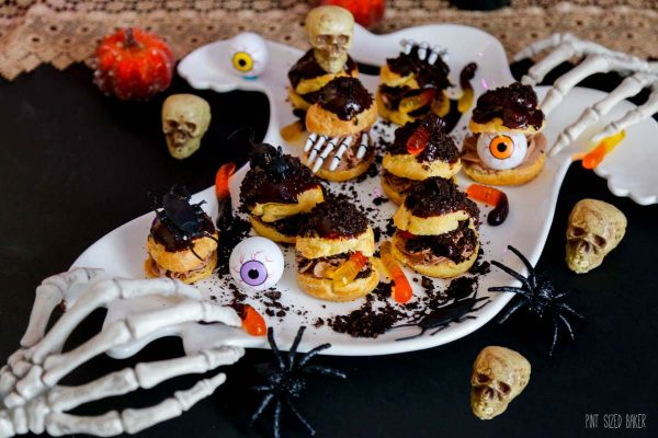 Tasty cream puffs decorated for Halloween with gummy worms, fake spiders, skeleton hands, and plastic eyeballs.