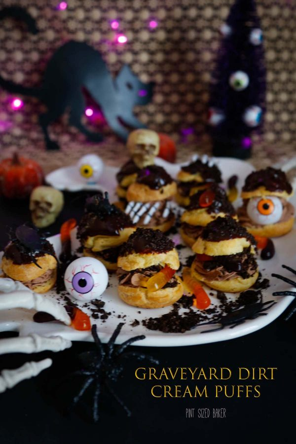 Serve up these fun and easy Graveyard Dirt Cream Puffs for your Halloween party. They are stuffed with chocolate whipped cream and fun candies.
