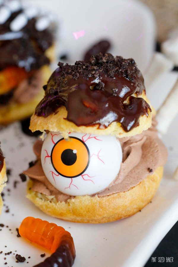 A cream puff with chocolate whipped cream and chocolate ganache on top with a plastic eyeball to make it spooky.
