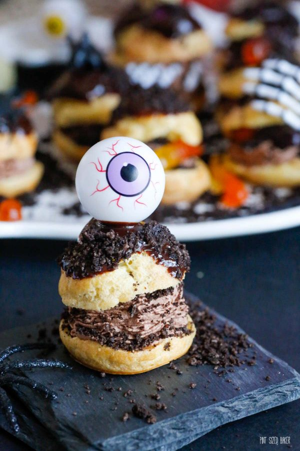 A cream puff with chocolate whipped cream, Oreo crumbs, and chocolate ganache on top with a plastic eyeball on top to make it spooky.