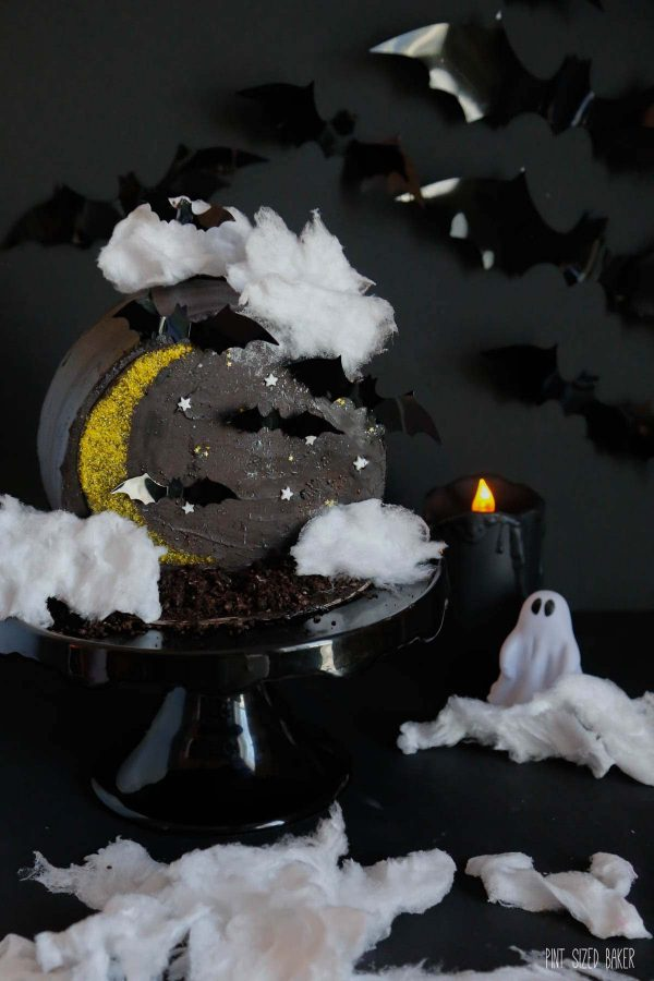 A Halloween inspired cake with a crescent moon, cotton candy clouds and bats on the cake.